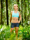 Athletic woman stretching before run in forest Royalty Free Stock Photography