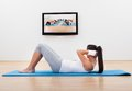 Athletic woman working out at home barefoot young women lying on a mat doing liftups and head raises while watching and Stock Photos