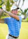 Athletic young man playing golf golfer hitting fairway shot swinging club Royalty Free Stock Photos