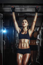 Athletic young sexy girl pulls up on bar in the gym Royalty Free Stock Photo