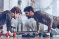 Athletic young sportsmen doing push ups with dumbbells at the gym Royalty Free Stock Photo