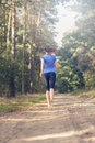 Athletic young woman jogging along a forest track in sportswear away from the camera in fitness and wellness concept Royalty Free Stock Photos