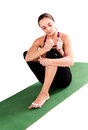 Athletic young woman practicing yoga pose and making manicure is Royalty Free Stock Photo