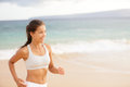 Athletic young woman running on the beach happy in sportswear jogging by ocean training to maintain her fitness female sport Royalty Free Stock Photography