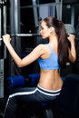 Athletic young woman works out on training gym equipment Stock Image