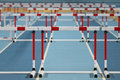 Athletics record attempt races barriers over a running track in hall Stock Photo