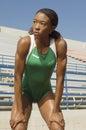 Atleta femminile standing with hands sulle ginocchia Immagine Stock