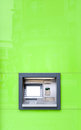 Atm machine in green wall shining in sun or cash with weak reflection of building and people fast and convenient way of cash out Stock Photo