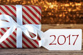 Atmospheric christmas gift with label text macro of or present on wooden background card for seasons greetings best wishes or Royalty Free Stock Image