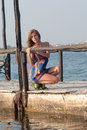 Atmospheric photo at the pier blond slim woman in dress sitting on legs and enjoying summer holidays Royalty Free Stock Photos