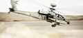 Attack Apache longbow helicopter gunship flying fast and low with dust debris in its wake. Royalty Free Stock Photo