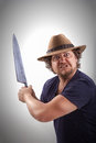 Attacker with big knife a very angry looking man is holding a very looking straight in the camera picture dodge and burn effect Stock Photo
