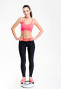 Attactive smiling young fitness woman standing on weighing scale Royalty Free Stock Photo