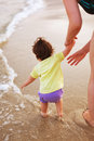 Attending baby on sea shore wanting to get to water Stock Photo