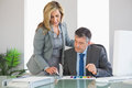 Attentive businesswoman explaining figures to a businessman blonde an mature at Royalty Free Stock Photo