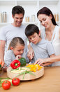 Attentive parents cooking with their children Stock Photos