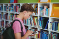 Attentive schoolboy using digital tablet in library Royalty Free Stock Photo