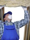 Attic thermal insulation worker thermally insulating a house using mineral wool Stock Photography