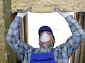 Attic thermal insulation worker thermally insulating a house using mineral wool Stock Image