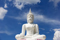 The attitude of meditation white buddha against blue sky. Royalty Free Stock Photo