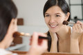 Attractiv happy woman applying makeup attractive smiling with her long brunette hair in a mirror leaning forwards to see better as Stock Photo