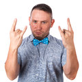 Attractive adult man with beard in a blue bow tie in summer shirt showing gesture hands of rock Royalty Free Stock Photo