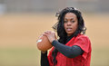 Attractive african american woman football player young in red practice mesh jersey holding a generic ready to throw Royalty Free Stock Photos