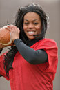 Attractive african american woman football player young in red practice mesh jersey holding a generic ready to throw Stock Photography