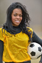 Attractive african american woman football soccer player young in yellow practice mesh jersey holding a generic ball Royalty Free Stock Image