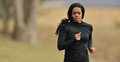 Attractive african american woman jogger runner young in black fitness gear jogging in a park cold weather Royalty Free Stock Photography
