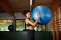 Attractive afro girl with curly hair smiling at gym young cheerful woman standing fit ball in fitness center Stock Photo