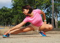 Attractive Asian woman stretches after jogging Royalty Free Stock Photo