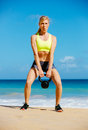 Attractive athletic woman doing kettle bell workout young exercises outside fitness working out at the beach crossfit exercise Royalty Free Stock Images