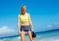 Attractive athletic woman doing kettle bell workout young exercises outside fitness working out at the beach crossfit exercise Stock Photography