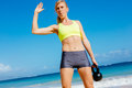 Attractive athletic woman doing kettle bell workout young exercises outside fitness working out at the beach crossfit exercise Stock Photo