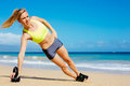 Attractive athletic woman doing kettle bell workout young exercises outside fitness working out at the beach crossfit exercise Stock Images