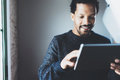 Attractive bearded African businessman using tablet while standing at his modern home office.Concept of young people