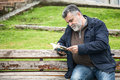 Attractive bearded man reading in a park Royalty Free Stock Photo