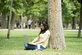 Attractive beautiful latin woman happy working on her laptop outside in a green park Royalty Free Stock Photo