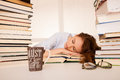 Attractive beautiful tired student sleeps on pile of books with Royalty Free Stock Photo