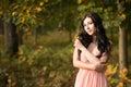 Attractive beautiful woman. Nature, autumn, fall yellow leafs. Fashion orange dress