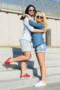 Attractive best friends outdoor friendship standing on the stairs Stock Photos