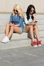 Attractive best friends outdoor friendship texting on the stairs Royalty Free Stock Photography
