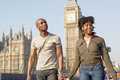 Attractive black tourist couple holding hands and walking past big ben while visiting london city on vacation Royalty Free Stock Image