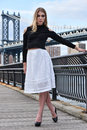 Attractive blond fashion model posing pretty on the pier with Manhattan Bridge on the background. Royalty Free Stock Photo