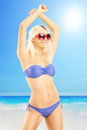 Attractive blond female in bikini wearing sunglasses on beach next to a sea Royalty Free Stock Image