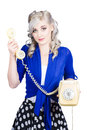 Attractive blond female secretary on vintage phone handing over the receiver yellow its for you Royalty Free Stock Images