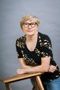 Attractive blond senior woman wearing glasses sitting with clasped hands in a relaxed position smiling at the camera on grey Stock Photo