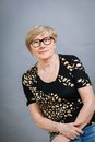 Attractive blond senior woman wearing glasses sitting with clasped hands in a relaxed position smiling at the camera on grey Stock Photography