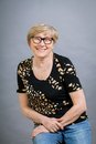 Attractive blond senior woman wearing glasses sitting with clasped hands in a relaxed position smiling at the camera on grey Royalty Free Stock Image